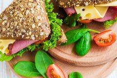 Сандвич бургера с ветчиной, сыром, томатами и салатом Стоковые Изображения RF