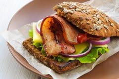 Сандвич бургера с салатом, беконом, сыром, луком и кетчуп на бумаге Стоковая Фотография RF