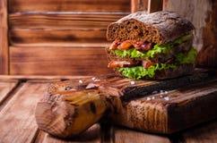 Сандвич бургера с салатом, зажаренным в духовке беконом на темной деревянной разделочной доске Селективный фокус Стоковая Фотография RF