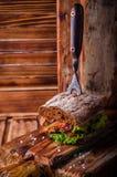 Сандвич бургера с салатом, зажаренным в духовке беконом на темной деревянной разделочной доске Селективный фокус Стоковые Изображения RF