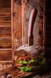 Сандвич бургера с салатом, зажаренным в духовке беконом на темной деревянной разделочной доске Селективный фокус Стоковое фото RF