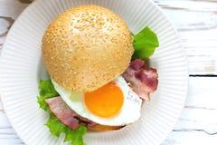Сандвич бургера с яичницей, беконом и салатом Стоковые Изображения RF
