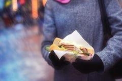 Сандвич в руках ` s женщины Еда улицы Стоковые Фотографии RF