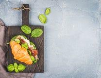 Сандвич круассана с копчеными di Пармой ветчины мяса, солнцем высушил томаты, свежий шпинат и базилик на темное деревянном Стоковые Фото