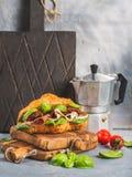 Сандвич круассана с копчеными di Пармой ветчины мяса, солнцем высушил томаты, свежий шпинат и базилик на текстурированном камне Стоковые Изображения RF