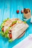 Сандвич пита заполненный с цыпленком, яичком, салатом, сыром, томатом вишни на голубой древесине Стоковая Фотография