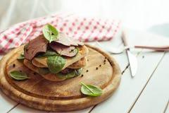 Сандвич ростбифа с салатом и перцем на деревенской деревянной плите тонизировать Стоковая Фотография