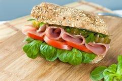 Сандвич с ветчиной, соленьями, перцем, салатом и томатом на доске и салфетке стоковые фото