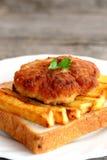 Сандвич с зажаренной котлетой картошек и мяса Турции на плите и на старом деревянном столе closeup Стоковая Фотография