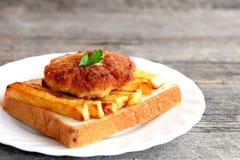 Сандвич с зажаренными картошками и котлетой мяса на плите и на старом деревянном столе closeup Стоковые Изображения RF
