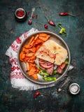 Сандвич с хлебом ciabatta, зажаренным в духовке мясом, овощами и сладким картофелем в плите на деревенской деревянной предпосылке стоковые фото