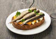 Сандвич с шпротинами и яичком на деревянном столе Стоковое Фото