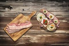 Сандвич томата ветчины и сыра и вишни с Rashers бекона на разделочной доске, комплекте на старой деревянной поверхности таблицы с Стоковое Изображение