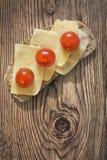 Сандвич томата сыра и вишни на старом деревянном блоке Стоковая Фотография
