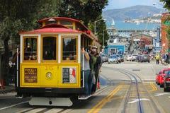 Сан-Франциско, Калифорния - Mai 23, 2015: Туристы ехать на иконическом фуникулере, дне голубого неба наверху overloo взгляда улиц Стоковое Изображение