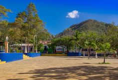 Сан-Хуан del Sur, Никарагуа - 11-ое мая 2018: Внешний взгляд парка при некоторые люди сидя на outdoors их домов внутри Стоковое Изображение RF