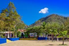 Сан-Хуан del Sur, Никарагуа - 11-ое мая 2018: Внешний взгляд парка при некоторые люди сидя на outdoors их домов внутри Стоковое Изображение