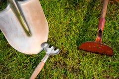 Сапка и лопаткоулавливатель на зеленой лужайке стоковые фото