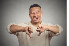 Саркастический молодой человек показывая 2 большого пальца руки вниз подписывает жест рукой Стоковое Изображение