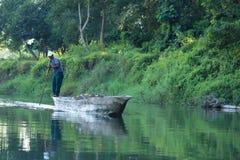 Сафари человека canoeing на деревянных пирогах шлюпки на реке Rapti, в национальном парке Chitwan, Непал стоковые фото