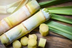 сахарный тростник и зеленая часть сахарного тростника отрезка лист на предпосылке деревянного стола стоковые фотографии rf