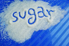 Сахар слова написанный против сахара на сини Стоковое фото RF