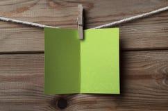 Салатовая поздравительная открытка прикреплянная к строке на деревянной предпосылке Стоковое Изображение