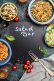 Салат-бар с различным здоровым вегетарианским блюдом салатов, forg и черной доской, взгляд сверху, рамкой Салат-бар надписи на пр Стоковые Фото