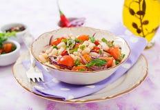 Салат белых фасолей, томата, arugula, красного лука и перца в шаре Стоковая Фотография