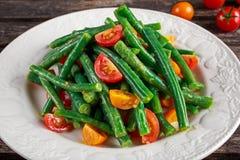 Салат зеленых фасолей с красными, желтыми томатами на белой плите Стоковые Изображения