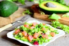 Салат копченых семг при смешивание, авокадо и оливковое масло и лимон салата одевая на плите Ингридиенты на деревянном столе Стоковые Фотографии RF