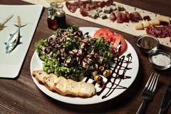 Салат мяса, хлеба, оливок и оливок, базилика на старой деревянной доске Черные томаты вишни зебры Стоковое Фото