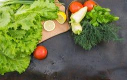Салат, отрезанный лимон на прерывая доске и корзина с toma Стоковые Фото