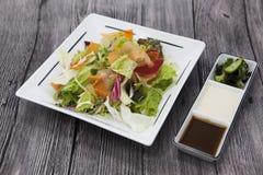 Салат от свежих листьев капусты, капусты цвета, морковей, луков на плите фарфора с соевым соусом и солениь Стоковое Изображение RF