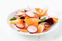Салат редиски моркови свеклы на белой плите Стоковое Изображение