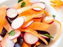 Салат редиски моркови свеклы на белой плите стоковое фото rf