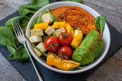 Салат с зажаренными овощами: зажаренные сладкие картофели, томаты, авокадоы, шпинат, тофу, Стоковое фото RF