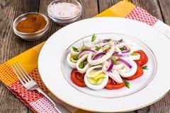 Салат с кальмаром, яичком и томатом на белой плите на предпосылке  Стоковые Фото