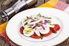 Салат с кальмаром, яичком и томатом на белой плите на предпосылке  Стоковая Фотография