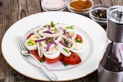 Салат с кальмаром, яичком и томатом на белой плите на предпосылке  Стоковые Фотографии RF