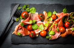 Салат с serrano jamon ветчины, томатами вишни, arugula, доской шифера Стоковое Изображение