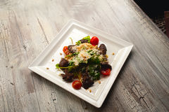 Салат цезаря с мясом, листьями и томатами на плите Стоковые Изображения