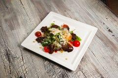 Салат цезаря с мясом, томатами и заскрежетанным пармезаном Стоковые Изображения