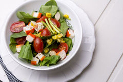 Салат шпината с томатами и мозолью вишни в шаре, белом деревянном столе Стоковое Фото