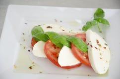 Салат Caprese с томатами, базиликом и моццареллой на таблице нержавеющей стали Стоковое Изображение