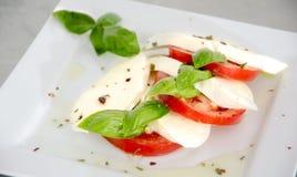Салат Caprese с томатами, базиликом и моццареллой на таблице нержавеющей стали Стоковое Изображение RF