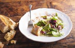 Салат Rucola на белой плите фарфора с хлебом brusheta Стоковые Фото