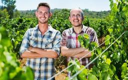 2 садовника стоя совместно в дворе дерева виноградин Стоковые Изображения