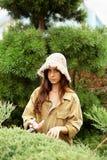 Садовник девушки в одеждах и соломенной шляпе деятельности режет scissoors сада вечнозеленые стоковое изображение