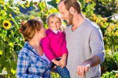 Садовничать семьи, стоя с вилкой в саде стоковое фото rf